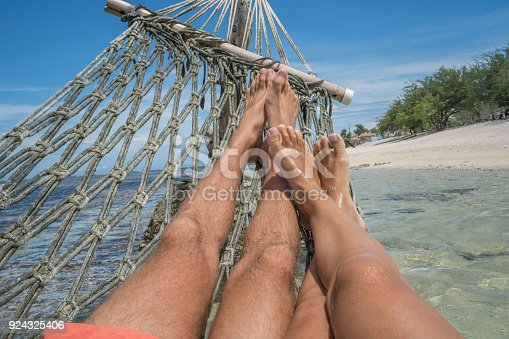 910783248 istock photo Personal perspective of couple relaxing on hammock over the sea, feet view 924325406