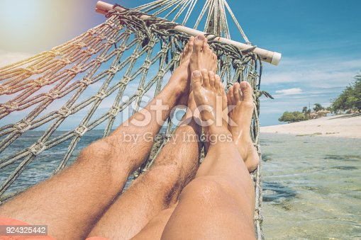 910783248 istock photo Personal perspective of couple relaxing on hammock over the sea, feet view 924325442