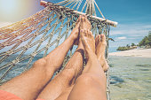 Couple's point of view from hammock on the sea, barefoot.\nPeople travel tropical climate concept.