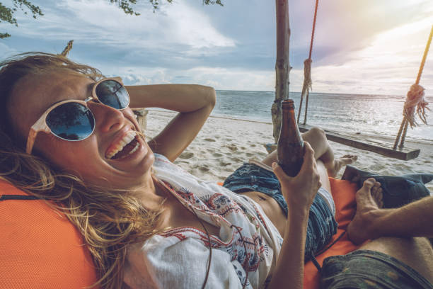 personal perspective of couple relaxing on the beach at sunset bar - woman leg beach pov stock photos and pictures