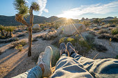 Personal perspective of couple relaxing on top of boulder rock at sunrise; feet view; \nPeople travel vacations relaxation concept
