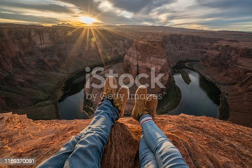 Personal perspective of couple relaxing on top of horseshoe bend in Arizona; feet view;  People travel vacations relaxation concept