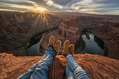 Personal perspective of couple relaxing on top of horseshoe bend in Arizona; feet view; \nPeople travel vacations relaxation concept