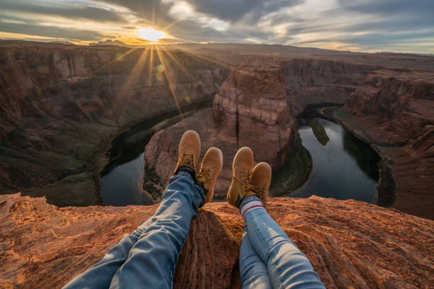 Personal perspective of couple relaxing on top of Grand Canyon; feet view;  People travel vacations relaxation concept stock photo