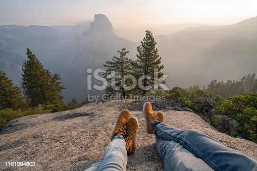 Personal perspective of couple relaxing on top of Yosemite valley; feet view;  People travel vacations relaxation concept