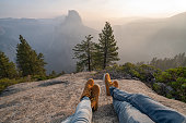 Personal perspective of couple relaxing on top of Yosemite valley; feet view; \nPeople travel vacations relaxation concept
