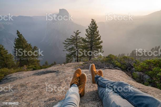 Photo of Personal perspective of couple relaxing on top of Yosemite valley; feet view