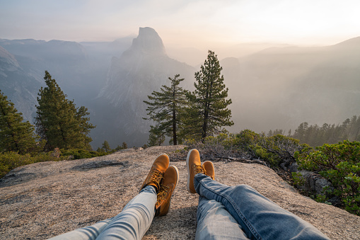 Personal perspective of couple relaxing on top of Yosemite valley; feet view
