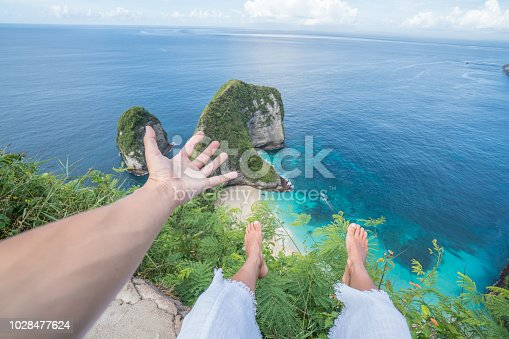 910785546 istock photo Personal perspective of female legs out on top of idyllic Kelingking beach in Bali Indonesia. People travel pov environment conservation concept. 1028477624