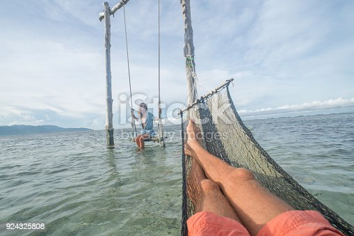 910783248 istock photo Personal perspective of man relaxing on hammock over the sea, woman on swing 924325808