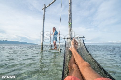 910783248 istock photo Personal perspective of man relaxing on hammock over the sea, woman on swing 924325958