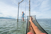 Couple's point of view from hammock on the sea, girl swinging. People travel tropical climate concept.