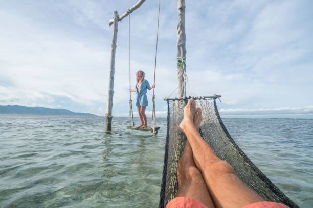 personal perspective of man relaxing on hammock over the sea, woman on swing - woman leg beach pov stock photos and pictures