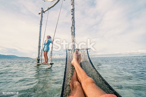 910783248 istock photo Personal perspective of man relaxing on hammock over the sea, woman on swing 924326016
