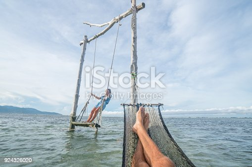 910783248 istock photo Personal perspective of man relaxing on hammock over the sea, woman on swing 924326020