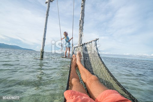 910783248 istock photo Personal perspective of man relaxing on hammock over the sea, woman on swing 924326072