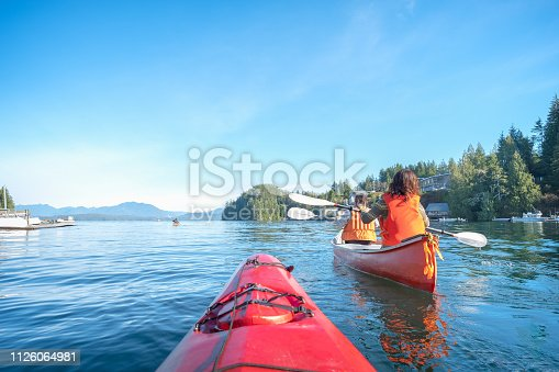 Mature mother and teen daughter enjoy morning kayaking and canoeing in rural Bamfield, British Columbia, Canada.