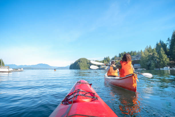 Personal Perspective of Ocean Kayaker Following Multi-Ethnic Family in Canoe Mature mother and teen daughter enjoy morning kayaking and canoeing in rural Bamfield, British Columbia, Canada. vancouver island stock pictures, royalty-free photos & images