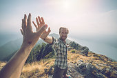 Personal perspective of Two hikers celebrating on mountain top with a high five