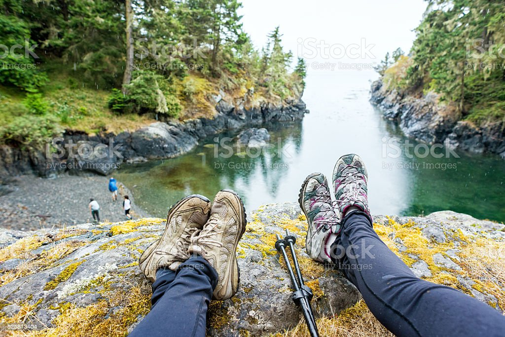 Personal Perspective of Two Hikers Sitting on Edge of Cliff stock photo