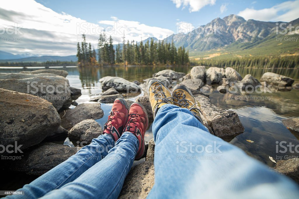 Personal perspective of two people relaxing on rocks by the lake....