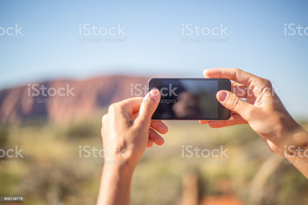 Personal perspective of woman photographing landscape using mobile phone stock photo