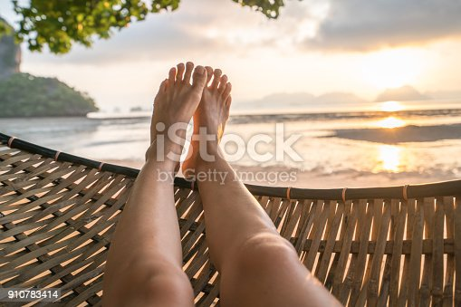910785546 istock photo Personal perspective of woman relaxing on hammock, feet view 910783414