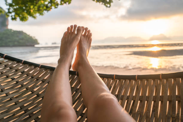 personal perspective of woman relaxing on hammock, feet view - woman leg beach pov stock photos and pictures