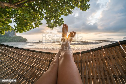 910785546 istock photo Personal perspective of woman relaxing on hammock, feet view 910785546