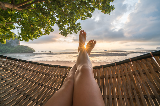 istock Personal perspective of woman relaxing on hammock, feet view 910785546