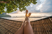 Female's point of view from hammock on the beach at sunrise, barefoot.