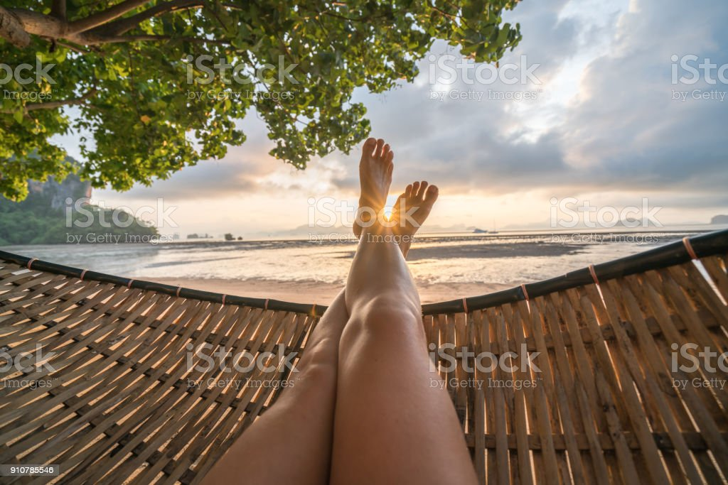 Personal perspective of woman relaxing on hammock, feet view stock photo