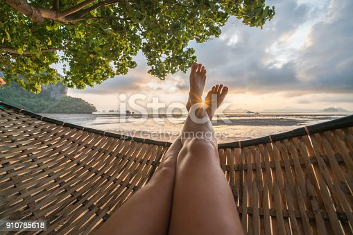 910785546 istock photo Personal perspective of woman relaxing on hammock, feet view 910785618