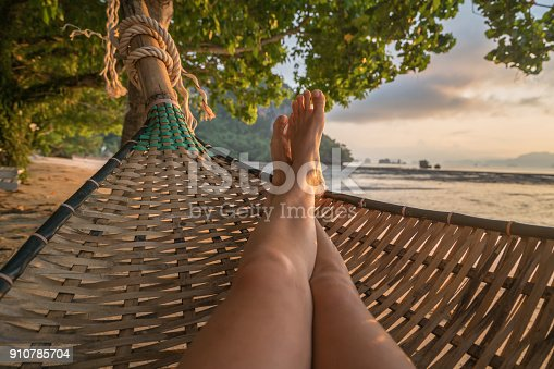 910785546 istock photo Personal perspective of woman relaxing on hammock, feet view 910785704
