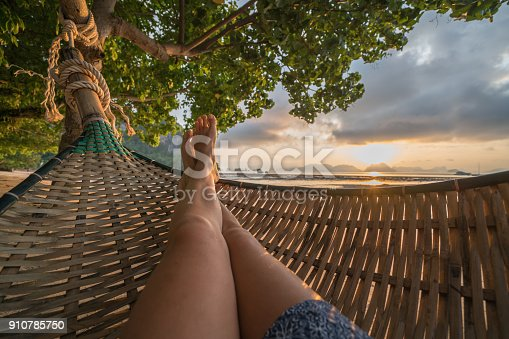 910785546 istock photo Personal perspective of woman relaxing on hammock, feet view 910785750