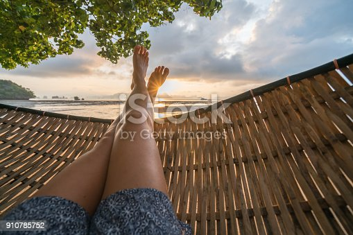 910785546 istock photo Personal perspective of woman relaxing on hammock, feet view 910785752