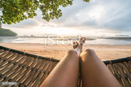 910785546 istock photo Personal perspective of woman relaxing on hammock, feet view 910785900