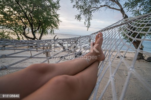 910785546 istock photo Personal perspective of woman relaxing on hammock, feet view 915105640