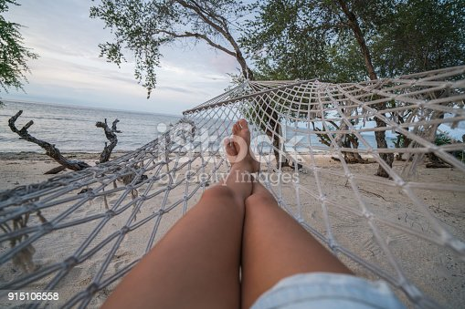 910785546 istock photo Personal perspective of woman relaxing on hammock, feet view 915106558