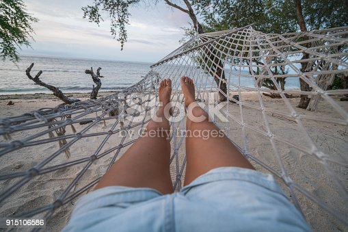910785546 istock photo Personal perspective of woman relaxing on hammock, feet view 915106586