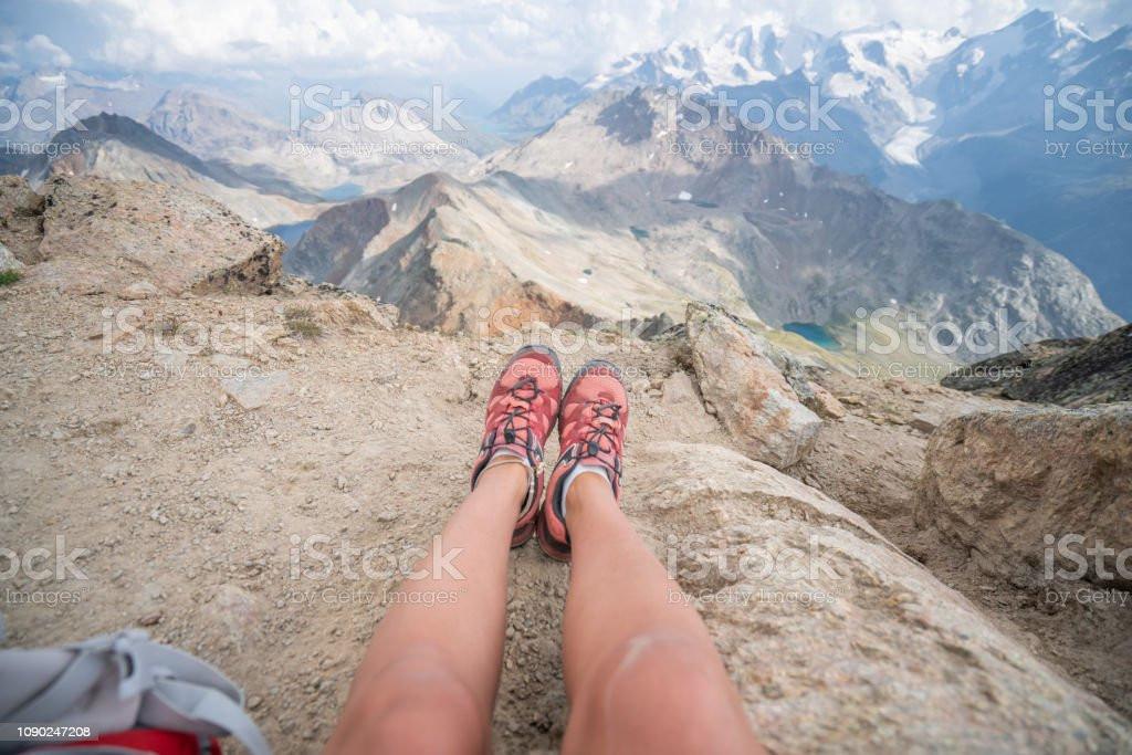 Personal perspective of woman sit-in gon mountain peak looking down...