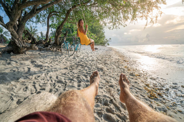personal perspective of young couple playing with swings on tropical beach in asia; people travel beach vacations holidays of happy couple having fun concept - woman leg beach pov stock photos and pictures