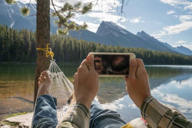 Persönliche Sicht der junge Mann am Hängematte zu entspannen und mit Handy – Foto