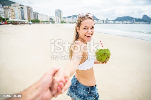 Woman in her 20s leading her partner by the hand onto a beach, smiling and affectionate, Copacabana Beach, Rio de Janeiro