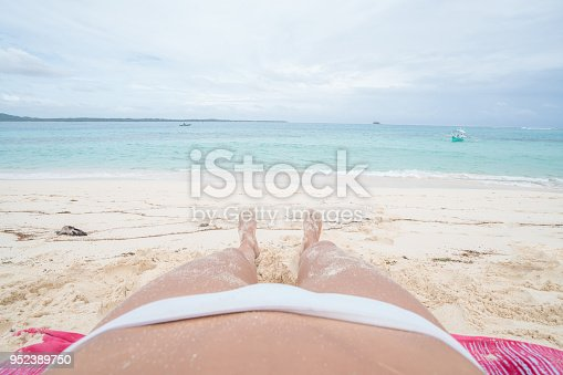 910785546 istock photo Personal perspective of young woman lying on tropical beach 952389750