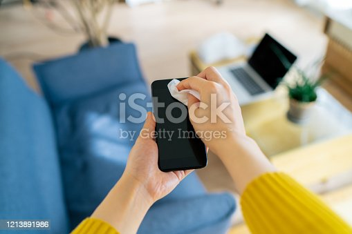 A personal perspective photo of a woman while wiping her phone with alcohol wet wipe at home.