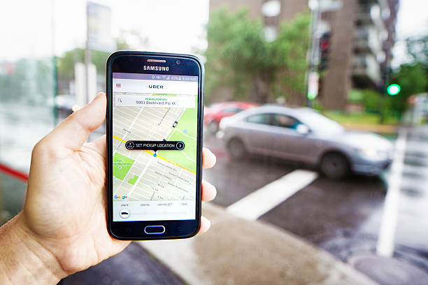 personal perspective view of hand holding phone ordering uber ride - rideshare stock photos and pictures