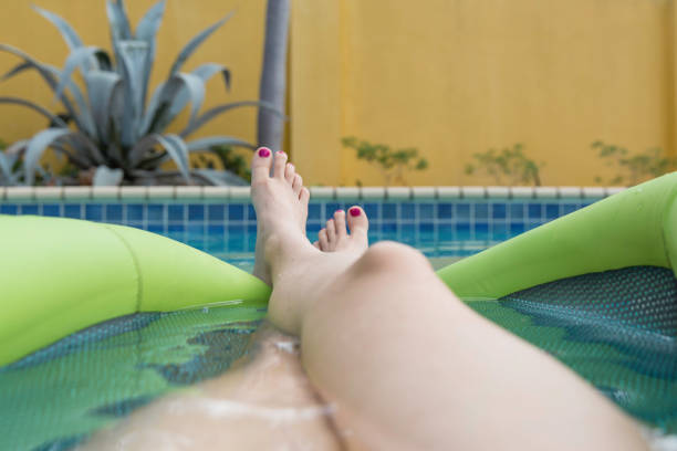 personal perspective woman floating on a green inflatable in swimming pool - woman leg beach pov stock photos and pictures