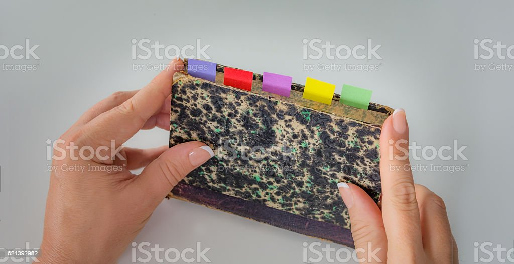 Personal perspective woman holding an old book with color tabs stock photo