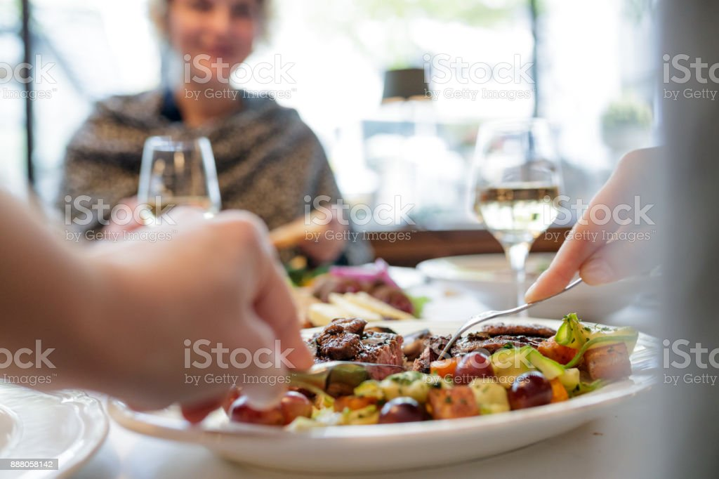 Personal point of view of woman cutting steak stock photo